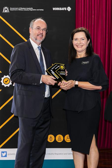 Minister Bill Johnston presenting Melody Miles, Bethesda Health Care with the winning trophy for 'Best workplace safety and health management system'